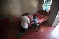 """Using a bed as a desk, Agustin Vazquez helps his sons Samuel and Hector with their schoolwork handed out by teachers amid the new coronavirus pandemic at their home in Nuevo Yibeljoj, Chiapas state, Mexico, Friday, Sept. 11, 2020. """"I try, but it's not the same as a teacher, because I'm a farmer,"""" said Agustín. (AP Photo/Eduardo Verdugo)"""