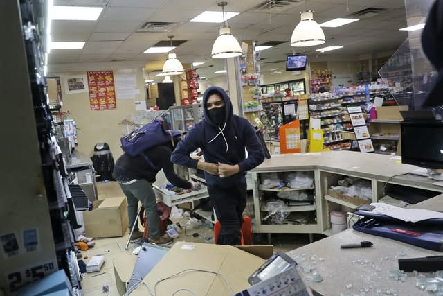 People look through a 7-Eleven store after they entered through a smashed window in New York