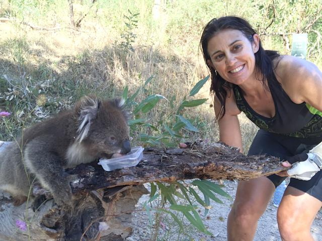 The cyclist Anna Heusler providing water to a koala (Caters)