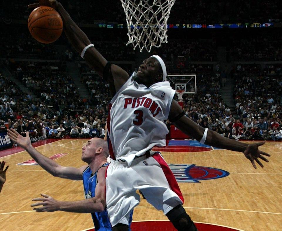 Pistons' Ben Wallace grabs a rebound past Orlando Magic's Pat Burke during the fourth quarter April 30, 2003 in Game 5 of the first round of the playoffs at the Palace of Auburn Hills.