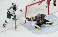 Vegas Golden Knights goaltender Marc-Andre Fleury (29) knocks the puck away from Minnesota Wild right wing Ryan Hartman (38) during the second period of an NHL hockey game Tuesday, Dec. 17, 2019, in Las Vegas. (AP Photo/John Locher)