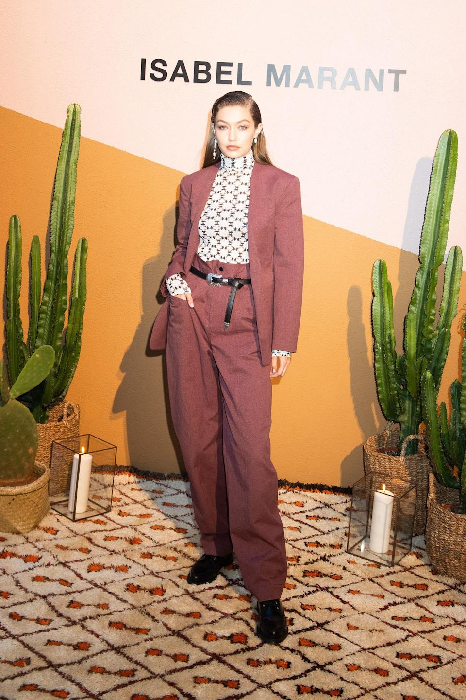 After walking the Versace Men's runway, Gigi changed into a burgundy suit with a patterned turtleneck to attend the designer Isabel Marant's afterparty. She paired her slicked-back side part with asymmetrical earrings — boss moves if we've ever seen 'em!
