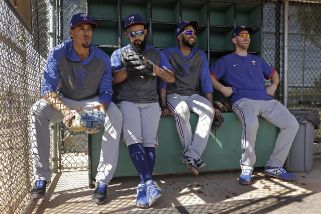 Texas Rangers players from left, Ronald Guzman, Rougned Odor, Elvis Andrus and Todd Frazier wait in the dugout to start batting practice during spring training baseball workouts Monday, Feb. 17, 2020, in Surprise, Ariz. (AP Photo/Charlie Riedel)
