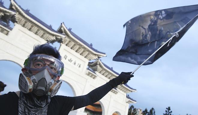 A Hong Kong protester in Taiwan waves a flag marking the first anniversary of a mass rally in Hong Kong against a since-withdrawn extradition bill. Photo: AFP
