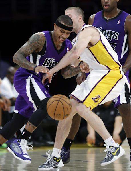 Sacramento Kings guard Isaiah Thomas, left, is fouled by Los Angeles Lakers guard Steve Blake (5) in the first half of an NBA basketball game in Los Angeles, Sunday, March 17, 2013. (AP Photo/Reed Saxon)