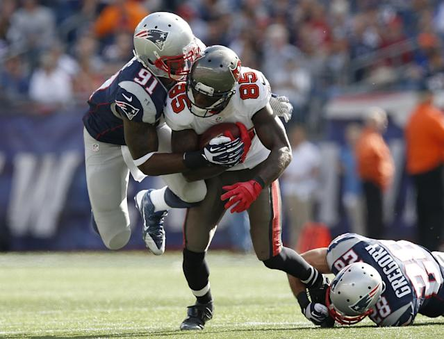 New England Patriots outside linebacker Jamie Collins (91) and strong safety Steve Gregory (28) tackle Tampa Bay Buccaneers wide receiver Kevin Ogletree (85) in the second half of an NFL football game Sunday, Sept. 22, 2013, in Foxborough, Mass. (AP Photo/Elise Amendola)