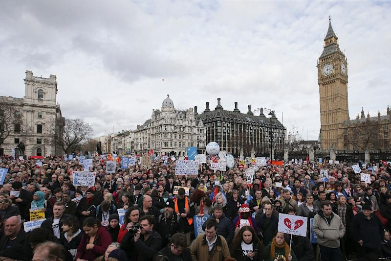 Demonstrators with placards gather in Parliament Square to protest with the Houses of Parliament and Big Ben in the background during a rally against cuts to NHS funding in central London on March 4, 2017