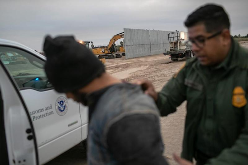 A border patrol agent detains an undocumented immigrant near a section of privately-built border wall under construction on 11 December 2019 near Mission, Texas.