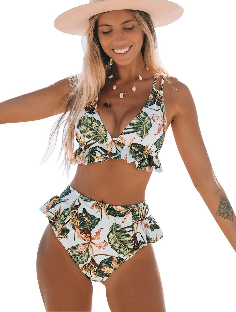 """<strong><em>Telaura High Waisted Ruffle Bikini</em></strong><br><br>Flutter your way to the seaside with this reviewer-approved two piece. """"Was hesitant to get this, but I just sized up and I'm so glad I did! I'm 5' 4"""" at about 165 pounds, athletic build — larger at the bottom — and this high waisted bikini bottom hugs my curves so nicely and the ruffles are so cute! I highly recommend but size up at least one full size.<br><br><br><strong>Telaura</strong> High Waisted Ruffle Bikini, $, available at <a href=""""https://amzn.to/2SbbSDZ"""" rel=""""nofollow noopener"""" target=""""_blank"""" data-ylk=""""slk:Amazon"""" class=""""link rapid-noclick-resp"""">Amazon</a>"""