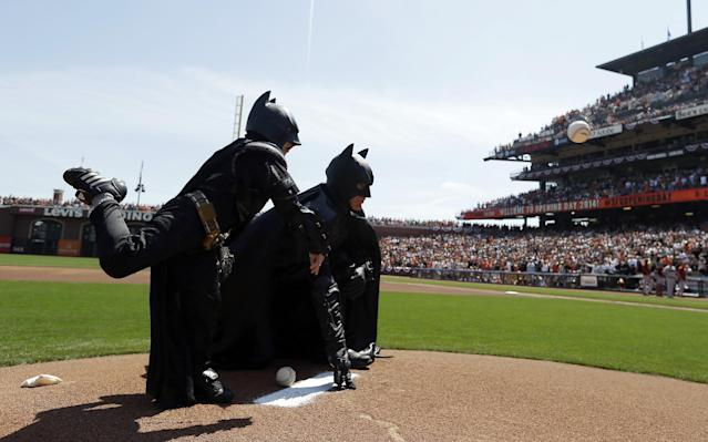 Miles Scott, left, dressed as Batkid, throws the ceremonial first pitch next to Batman before an opening day baseball game between the San Francisco Giants and the Arizona Diamondbacks in San Francisco, Tuesday, April 8, 2014. On Nov. 15, 2013, Scott, a Northern California boy with leukemia, fought villains and rescued a damsel in distress as a caped crusader through The Greater Bay Area Make-A-Wish Foundation. (AP Photo/Eric Risberg, Pool)
