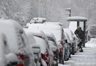 A man brushes snow of a car in Braco, near Dunblane in Scotland.