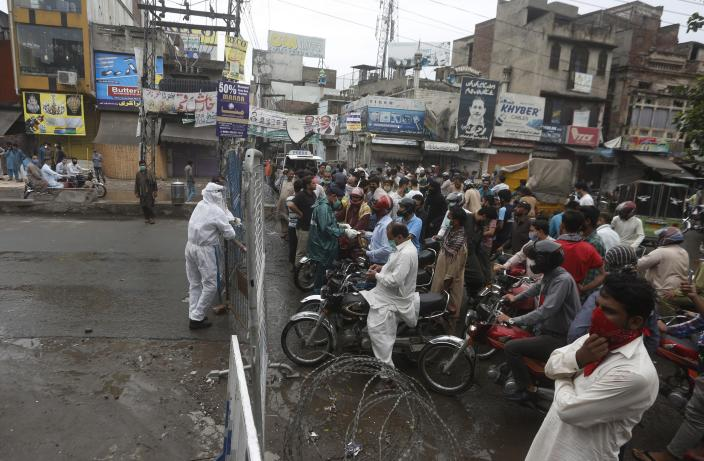 FILE - In this Thursday, June 25, 2020 file photo, police officers stop motorcyclists from entering a restricted area that is sealed off to control the spread of the coronavirus, in Lahore, Pakistan. For months, experts have warned of a potential nightmare scenario: After overwhelming health systems in some of the world's wealthiest regions, the coronavirus gains a foothold in poor or war-torn countries ill-equipped to contain it and sweeps through the population. (AP Photo/K.M. Chaudhry, File)