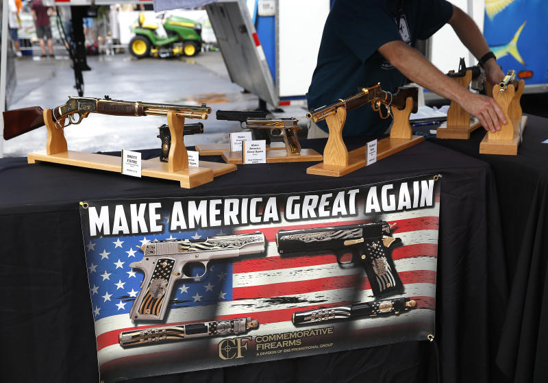 <strong>A worker rearranges the guns inside the booth at Commemorative Firearms as fans stopped by to check out guns bearing Trump's motto: 'Make America Great Again'  in Bristol, Tennessee</strong> (Boston Globe via Getty Images)