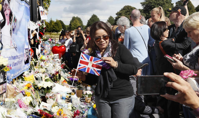 <p>A woman poses for a photograph as people crowd around the gates of Kensington Palace in London to pay tribute to the late Diana, Princess of Wales, Thursday, Aug. 31, 2017. Tributes at the gates are to mark the 20th anniversary of Diana's death, in a car crash in Paris on Aug. 31, 1997. (Photo: Kirsty Wigglesworth/AP) </p>