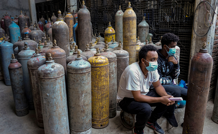 Men wait to refill their oxygen cylinders at Gast Solar Mechanics in Addis Ababa, Ethiopia - Friday 19 March 2021