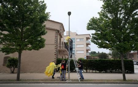 Members of Granoller's Committee for the Defence of the Republic hang yellow ribbons to demand the release of jailed Catalonian politicians in Granollers