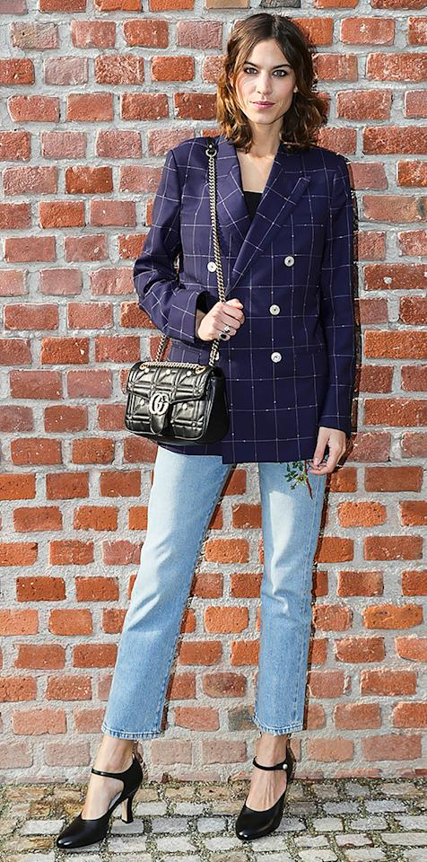 """<p>While in Milan for Fashion Week, Chung attended the Gucci show in a pair of straight-leg jeans, Mary Jane-inspired heels, a blue blazer, and classic black Gucci bag (get a similar style <a rel=""""nofollow"""" href=""""https://click.linksynergy.com/fs-bin/click?id=93xLBvPhAeE&subid=0&offerid=254155.1&type=10&tmpid=6894&RD_PARM1=https%3A%2F%2Fwww.net-a-porter.com%2Fus%2Fen%2Fproduct%2F802590%2FGucci%2Fgg-marmont-2-0-medium-embellished-quilted-leather-shoulder-bag&u1=ISAlexaChungStreetStyle3.22JA"""">here</a>). </p>"""