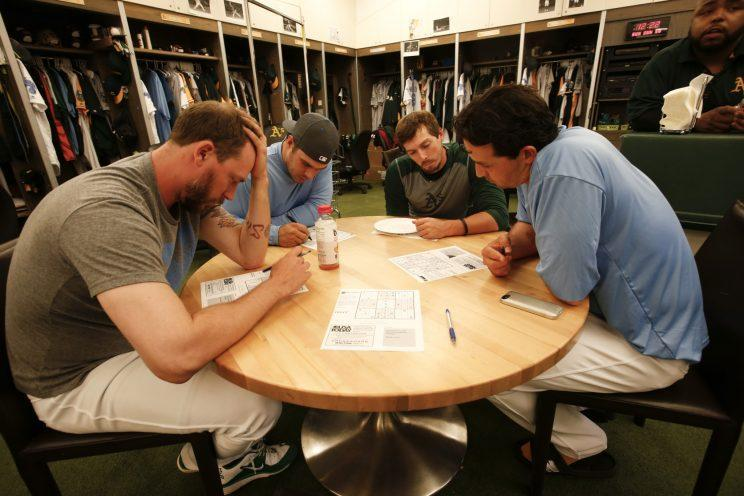 John Axford (left) works on a Soduku puzzle with teammates in the Oakland Athletics locker room. (Getty Images)