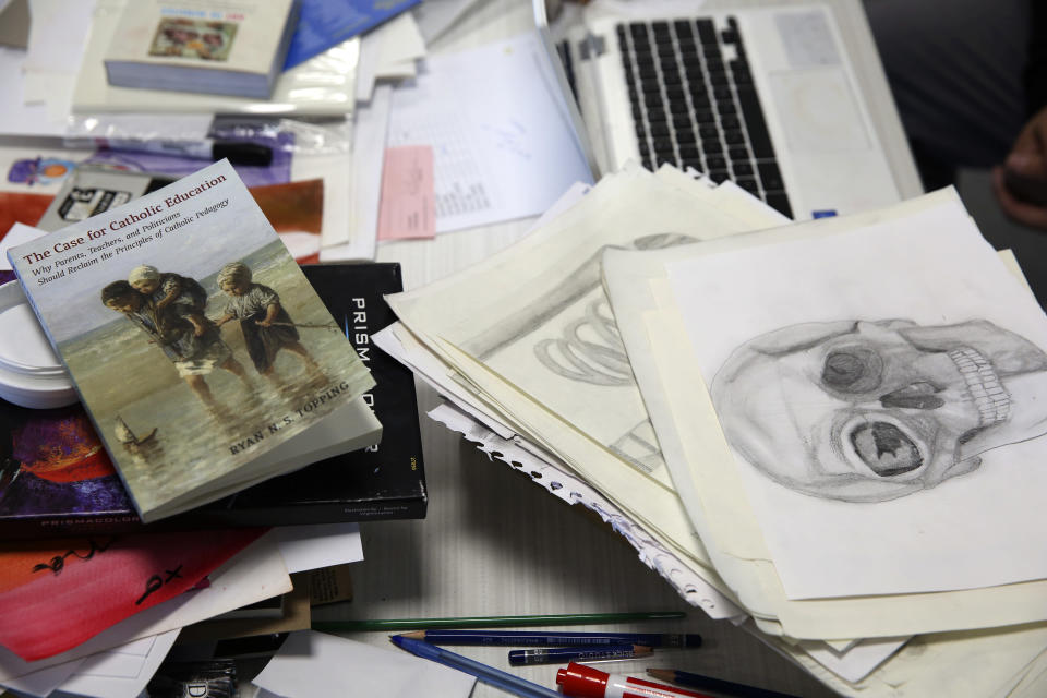 Books and drawings lie on the desk of an art teacher at the St. John Paul II Catholic School in Phoenix, Ariz., on Feb. 26, 2020. In the western suburbs of Phoenix, enrollment is surging at this new Catholic high school built to serve a fast-growing, heavily Hispanic community. (AP Photo/Dario Lopez-MIlls)