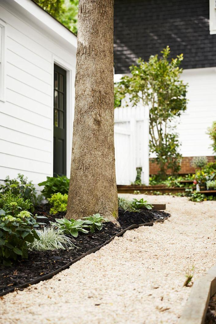 """<p>Pea gravel paths meander neatly through the yard, edged with 'Minuteman' hostas, Baby Gem boxwoods, 'Shamrock' Inkberry shrubs, and Endless Summer hydrangeas. """"The more hydrangeas, the better!"""" says Victoria.<br><br><strong>Get the Look: </strong><strong><strong><br>Landscape Design: </strong></strong>by <strong><a href=""""https://yardzen.com/"""" rel=""""nofollow noopener"""" target=""""_blank"""" data-ylk=""""slk:Yardzen"""" class=""""link rapid-noclick-resp"""">Yardzen</a></strong></p>"""