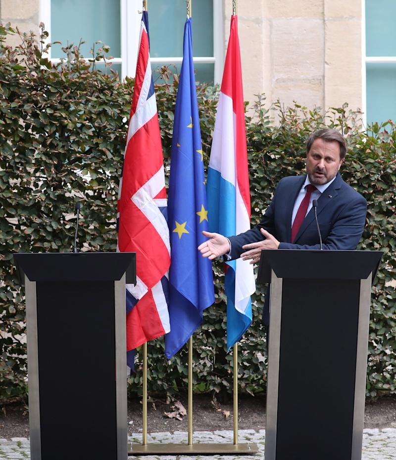 Luxembourg's PM Xavier Bettel gestures towards Boris Johnson's empty podium after his pulled out of a press conference