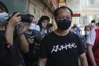 Spokesperson of Hong Kong Alliance in Support of Patriotic Democratic Movements of China Richard Tsoi, right, leaves after the group announced that it's disbanded in Hong Kong, Saturday, Sept. 25, 2021. The Hong Kong group that had organized annual vigils in remembrance of victims of the Chinese military's crushing of the 1989 Tiananmen Square pro-democracy protests voted to disband Saturday amid an ongoing crackdown on independent political activism in the semi-autonomous Chinese city. (AP Photo/Kin Cheung)