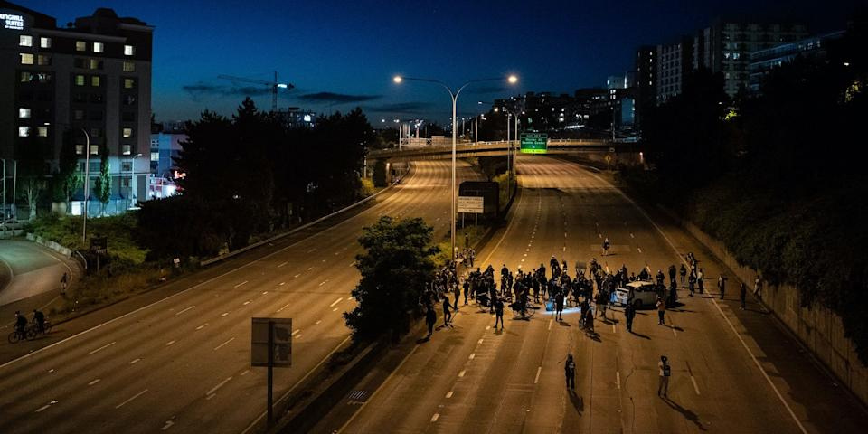 A car drove through a crowd of protesters on Seattle's Interstate 5 on Saturday, July 4, 2020. Protesters are seen on the freeway during another protest on June 24, 2020.