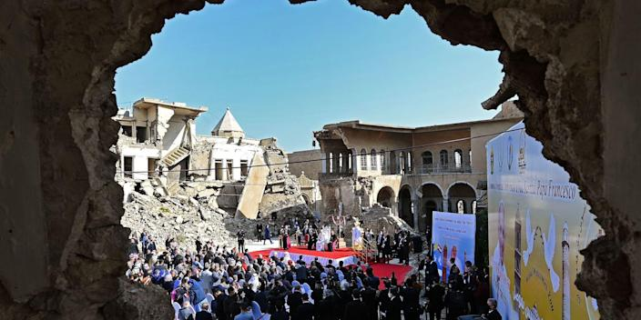 """Pope Francis speaks at a square near the ruins of the Syriac Catholic Church of the Immaculate Conception (al-Tahira-l-Kubra), in the old city of Iraq's northern Mosul on March 7, 2021. - Pope Francis, on his historic Iraq tour, visits today Christian communities that endured the brutality of the Islamic State group until the jihadists' """"caliphate"""" was defeated three years ago (Photo by Vincenzo PINTO / AFP) (Photo by VINCENZO PINTO/AFP via Getty Images)"""