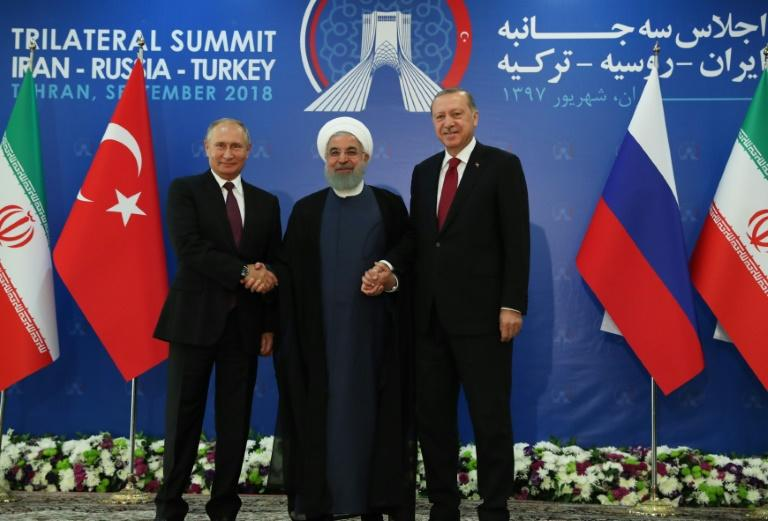 Turkish President Recep Tayyip Erdogan (R), Iranian President Hassan Rouhani (C) and Russian President Vladimir Putin (L) join hands during a three-way summit in Tehran on the Syrian conflict