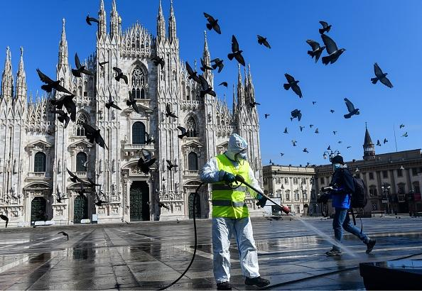 A man wearing protective gear, working for environmental services company AMSA, sprays disinfectant on Piazza Duomo in Milan.