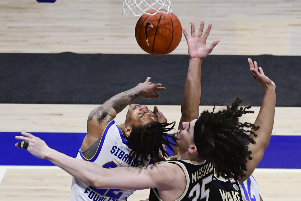 Pittsburgh forward Nike Sibande battles for a rebound with Wake Forest forward Ismael Massoud during the first half of an NCAA college basketball game, Tuesday, March 2, 2021, in Pittsburgh. (AP Photo/Fred Vuich)