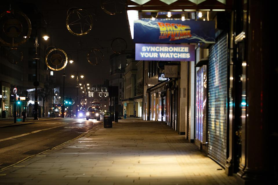 A taxi drives past temporarily closed shops and theatres on a near-deserted Strand in London, England, on January 7, 2021. England began a third national coronavirus lockdown earlier this week amid authorities' concern that the National Health Service (NHS) could soon be overwhelmed with covid-19 sufferers. Meanwhile, British Prime Minister Boris Johnson announced today that 1.5m people across the UK have now received at least a first dose of a covid-19 vaccine, with plans for hundreds of thousands of vaccinations to administered every day from the middle of this month, with military assistance. (Photo by David Cliff/NurPhoto via Getty Images)