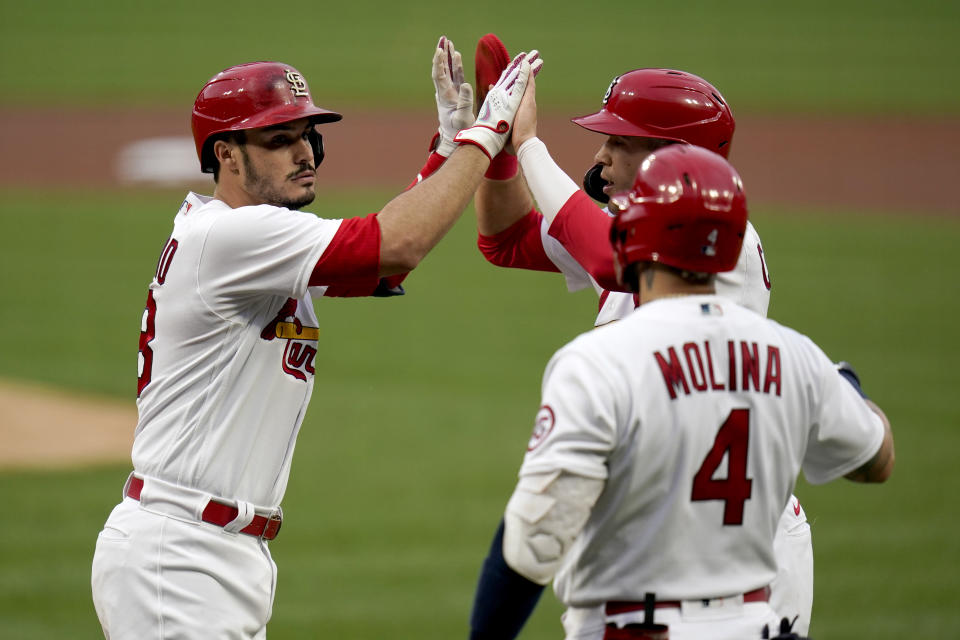 St. Louis Cardinals' Nolan Arenado, left, is congratulated by teammates Dylan Carlson and Yadier Molina (4) after hitting a two-run home run during the first inning of a baseball game Pittsburgh Pirates Tuesday, May 18, 2021, in St. Louis. (AP Photo/Jeff Roberson)