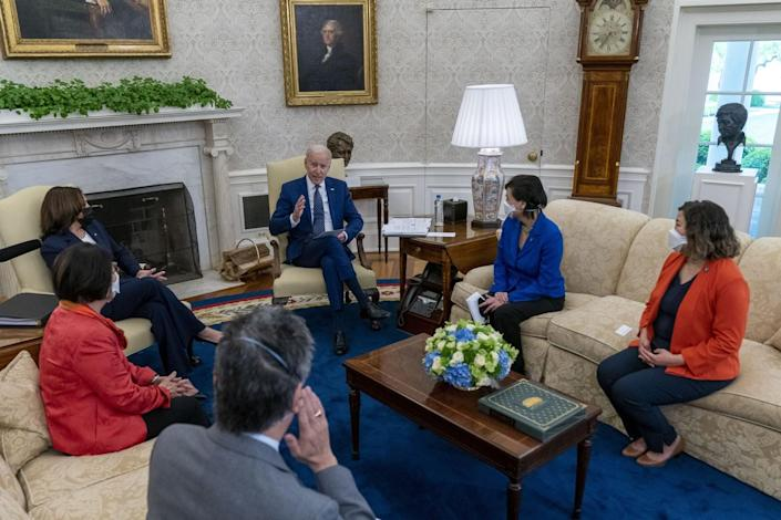 Biden speaks as he, Harris and four others are seated on couches and chairs in the Oval Office.