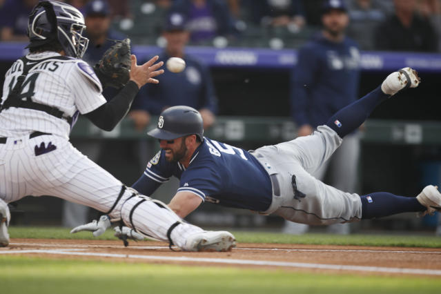 San Diego Padres' Greg Garcia, right, dives into home plate to score as Colorado Rockies catcher Tony Wolters catches the throw during the first inning of a baseball game Saturday, June 15, 2019, in Denver. Garcia doubled to lead off the game and then scored on a fielding error by left fielder David Dahl. (AP Photo/David Zalubowski)
