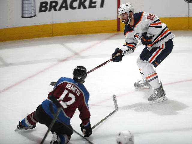 Edmonton Oilers center Sam Gagner, top, shoots the puck on the net as Colorado Avalanche defenseman Patrik Nemeth covers in the first period of an NHL hockey game Tuesday, April 2, 2019, in Denver. (AP Photo/David Zalubowski)