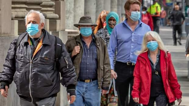 People follow Ottawa Public Health advice by wearing masks as they walk downtown in late April 2021. (Brian Morris/CBC - image credit)