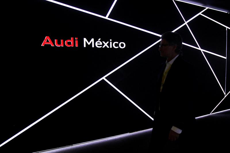 Man walks past the logo of Audi during the opening of a new plant in San Jose Chiapa