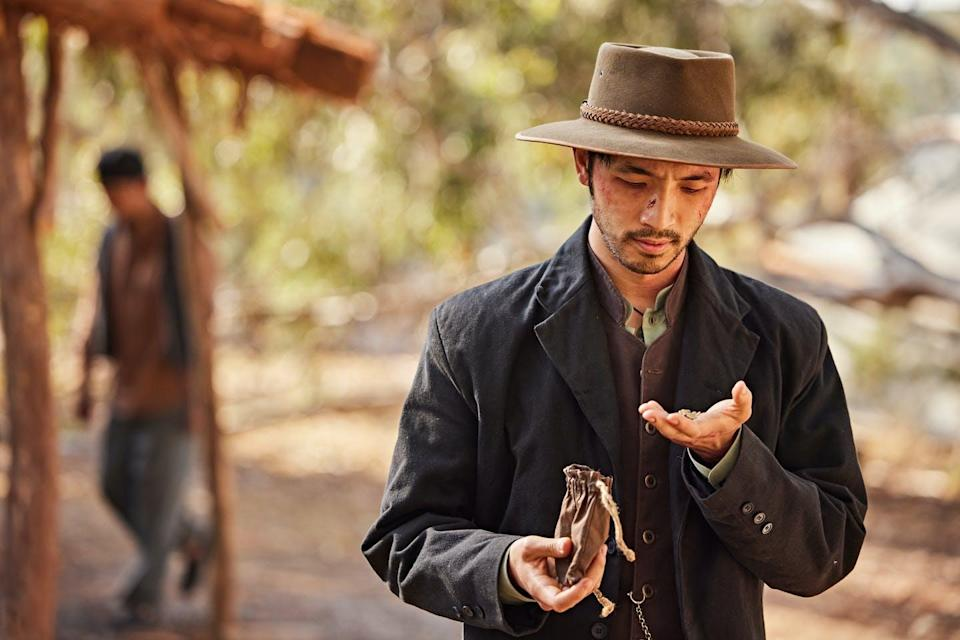 Production image: a Chinese man looks for gold in his hands.