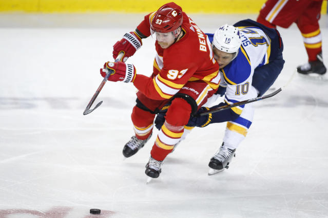 St. Louis Blues' Brayden Schenn, has the puck stolen by Calgary Flames' Sam Bennett during the third period of an NHL hockey game in Calgary, Saturday, Nov. 9, 2019. (Jeff McIntosh/The Canadian Press via AP)