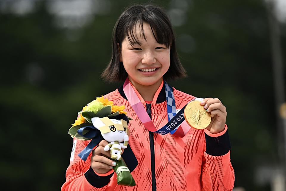 Japan's Momiji Nishiya poses with her gold medal during the podium ceremony of the skateboarding women's street final of the Tokyo 2020 Olympic Games at Ariake Sports Park in Tokyo on July 26, 2021. (Jeff Pachoud / Getty Images)