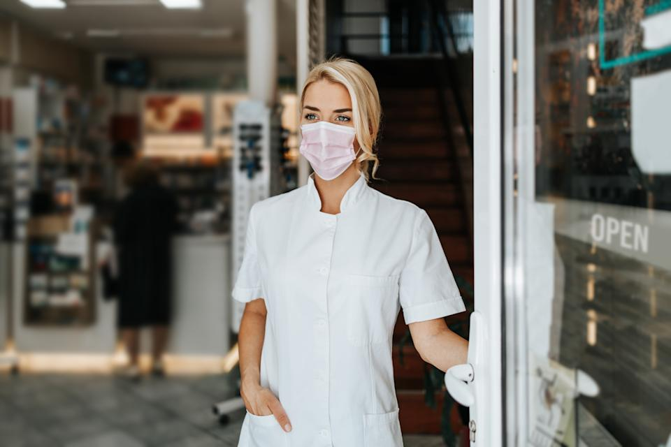 female pharmacist with face protective mask standing at open drugstore