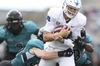Buffalo quarterback Matt Myers (10) breaks tackles by Coastal Carolina safety Brayden Matts, left, and Jacob Proche, right, to score a touchdown during the first half of a NCAA college football game in Buffalo, N.Y. on Saturday, Sept. 18, 2021. (AP Photo/Joshua Bessex)