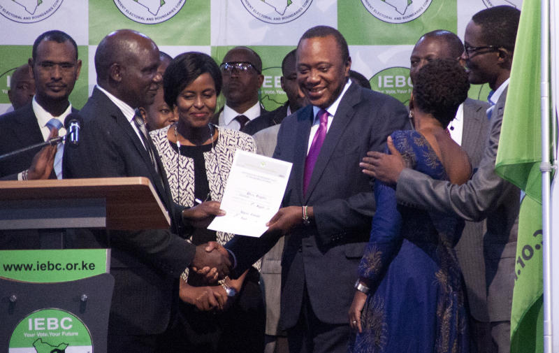 """The Chairman of the Independence Electoral and Boundaries Commission, Wafula Chebukati , left, hands over the certificate to Uhuru Kenyatta, centre right, after announcing him the winner in the presidentail race at the Centre in Bomas, Nairobi, Kenya, Friday, Aug.11, 2017. The commission said Kenyatta won Tuesday's election with 54 percent of the vote. It called the vote """"credible, fair and peaceful."""" (AP Photo/ Sayyid Abdul Azim)"""