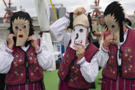 Folk dancers put on masks before performing during a ceremony marking 100 years of diplomatic relations between Japan and Romania, at the construction site of a suspension bridge over the Danube river in Braila, Romania, Thursday, Aug. 26, 2021. The bridge, built by Japanese and Italian companies, with a span of 1,974.3 meters, will be the largest of its kind in Romania and the third in the European union.(AP Photo/Vadim Ghirda)