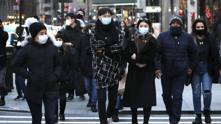 People wearing protective masks cross a street in Midtown on December 6, 2020 in New York City. (John Lamparski/Getty Images)