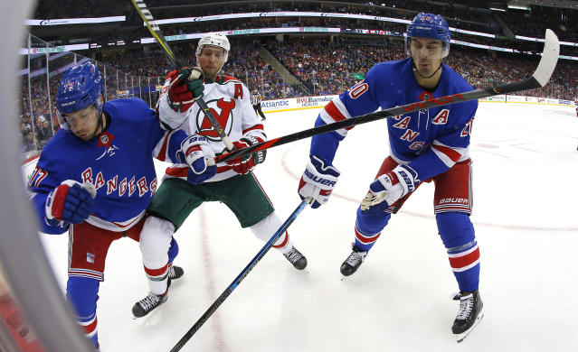 New York Rangers defenseman Tony DeAngelo (77) and Chris Kreider battle New Jersey Devils center Travis Zajac (19) for the puck during the second period of an NHL hockey game Saturday, Nov. 30, 2019, in Newark,N.J. (AP Photo/Noah K. Murray)