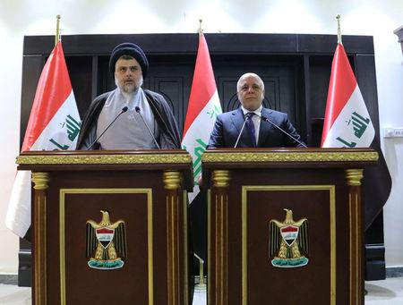Iraqi Shi'ite cleric Moqtada al-Sadr (L) speaks during a news conference with Iraqi prime Minister Haider al-Abadi in Baghdad