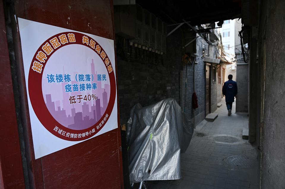 A man walks past a colour-coded sign which indicates the vaccination rate in a residential building is below 40 percent, part of a campaign to urge people to get vaccinated against the Covid-19 coronavirus in Beijing on April 7, 2021. (Photo by LEO RAMIREZ / AFP) (Photo by LEO RAMIREZ/AFP via Getty Images)