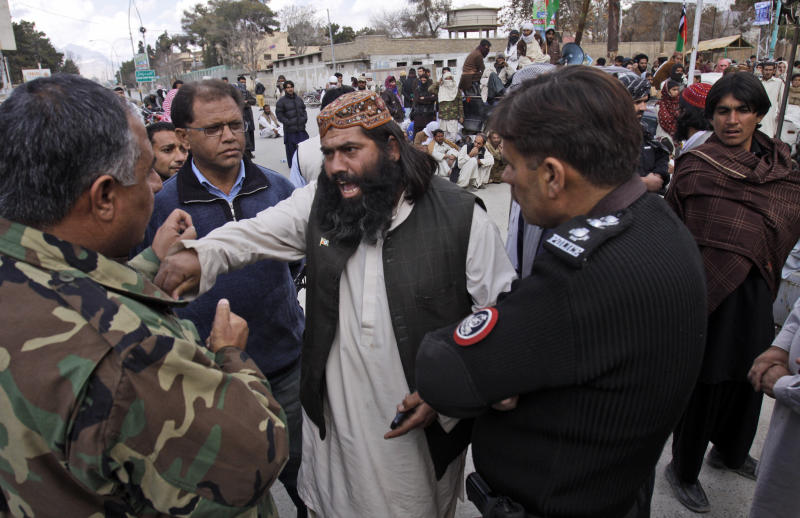 """In this Friday, Feb. 22, 2013, photo, provincial chief of Pakistani Sunni group Ahle Sunnat Wal Jamaat, Ramzan Mangal, center, argues with security officials, during a rally to condemn killings of their party activists by allegedly security forces, in Quetta, Pakistan. Pakistan's minority Shiite Muslims have begun to use words like """"genocide"""" to describe a violent spike in attacks directed against them by a militant Sunni group, with suspicious links to the country's security agencies and a mainstream political party that governs the largest province, where some of the most violent jihadi groups are headquartered. (AP Photo/Arshad Butt)"""